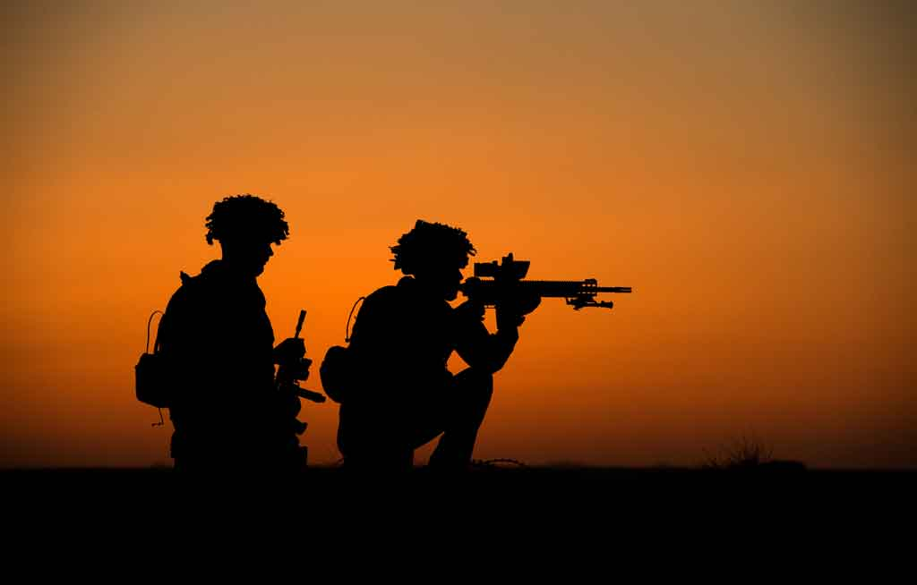 Soldiers of C Company 2nd Battalion Royal Anglian Regiment are silhouetted against the setting sun during operations in Afghanistan in June 2014.